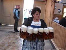 bar maid carrying 12 mugs of beer
