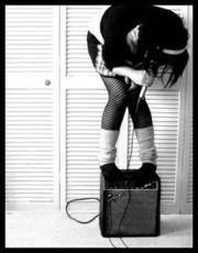 emo girl in fishnets standing on amp with mic